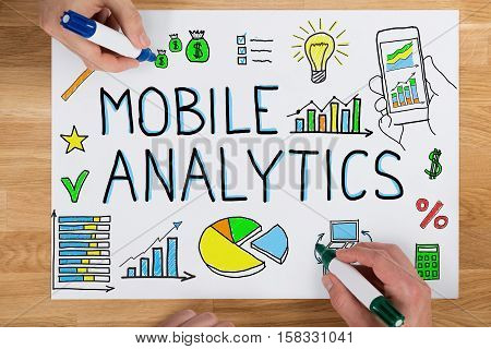 Close-up Of Two Businesspeople Drawing Mobile Analytic Concept On Paper Using Colorful Marker On Wooden Desk
