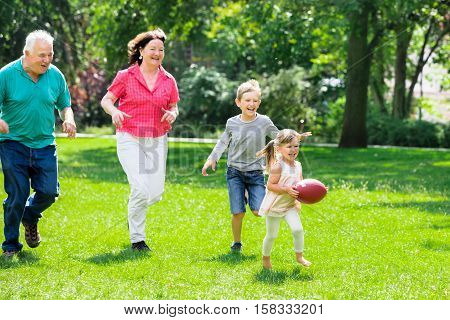 Happy Family Having Fun Playing With Rugby Ball In Park