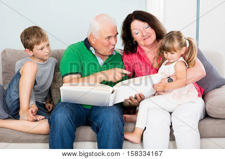 Family Looking At Photo Album With Children To Refresh Memory