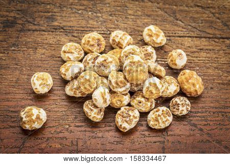 organic peeled tiger nuts, a rich source of resistant starch,a small pile against rustic, weathered wood