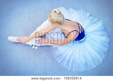 Portrait of a professional ballet dancer sitting on a floor. Female ballerina having a rest after performance or rehearsal. Ballet concept.
