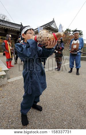 KAGAWA, JAPAN - NOVEMBER 20: boy is blowing a snail-trumpet of the start of the war at Marugame-castle Festival on November 20, 2016 in Japan.