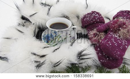 Winter background coffee mug snow, ermine and mittens
