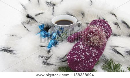 Winter background coffee mug snow, candy, ermine and mitten