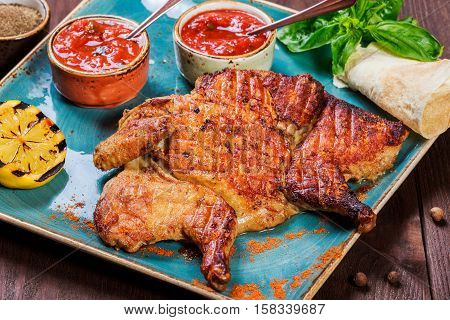 Roasted Chicken or turkey with spices and pita bread on plate on dark wooden background. Thanksgiving table served with knife and fork