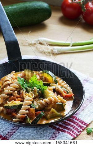 black iron pan with wholewheat pasta and zucchini tomato vegetables on a kitchen towel and a wooden worktop healthy vegetarian diet meal vertical selected focus narrow depth of field