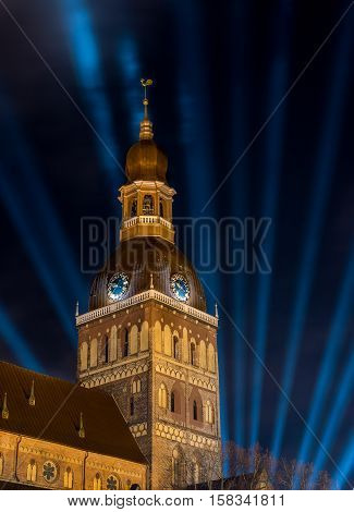 Church tower with clocks at night - blue floodlight in the dark sky