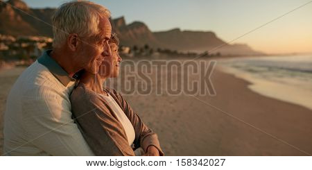 Loving Senior Couple Enjoying The Sunset At The Beach