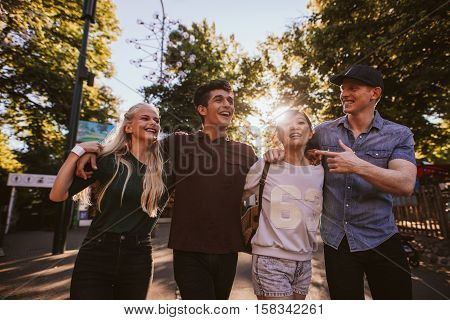 Four Friends Strolling In Amusement Park