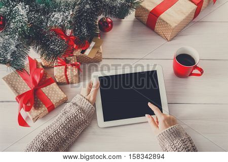 Christmas online shopping above view on wood. Female buyer touch screen of tablet, copy space. Woman has coffee, buys presents near christmas tree, among gift boxes. Winter holidays sales background