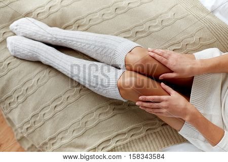 winter, clothes, fashion and people concept - close up of young woman legs in knee socks in bed at home