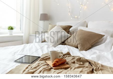 technology, holidays, christmas and winter concept - cozy bedroom with tablet pc computer, coffee cup and croissant on bed at cozy home