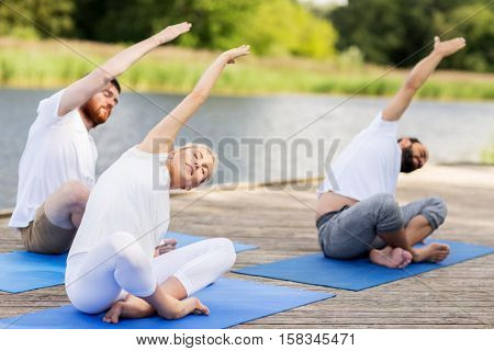 fitness, sport, and healthy lifestyle concept - group of people making yoga exercises outdoors on river or lake berth