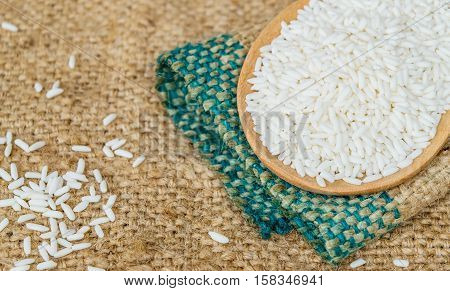 Glutinous rice in wooden spoon with hemp sacks background