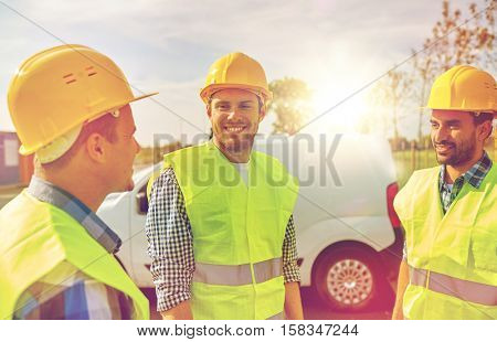 industry, building, construction and people concept - happy male builders in high visible vests outdoors