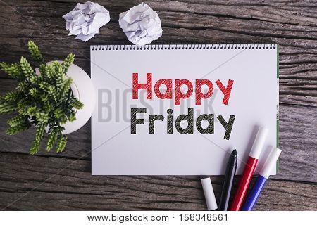 Notepad and green plant on wooden background with Happy Friday word