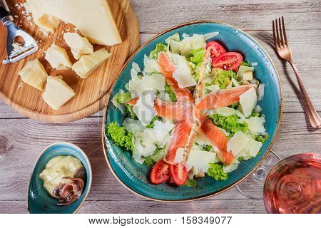 Salmon salad with tuna sauce parmesan cheese croutons tomatoes mixed greens lettuce and glass of wine on wooden background. Mediterranean food. Top view