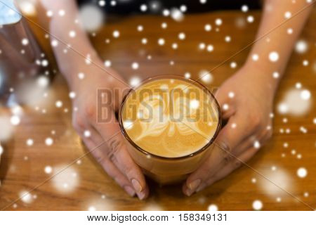 latte art, people and winter concept - close up of hands with butterfly etching in coffee cup over snow