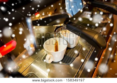 equipment, drinks and technology concept - close up of espresso machine making coffee over snow