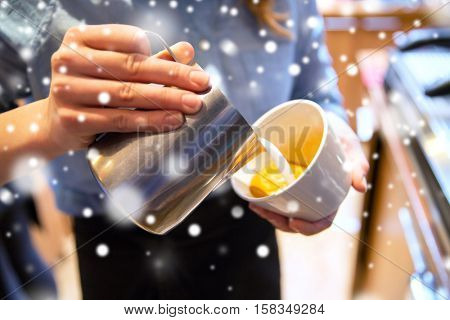 people, drinks and winter holidays concept - close up of woman pouring cream to cup of coffee at cafe bar or restaurant kitchen over snow