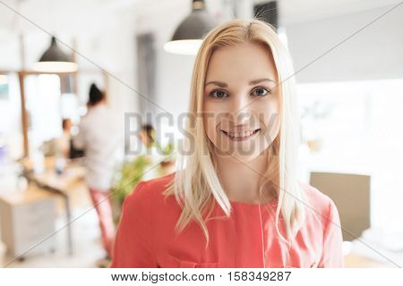 business, startup and people concept - happy businesswoman or creative woman at office or bureau