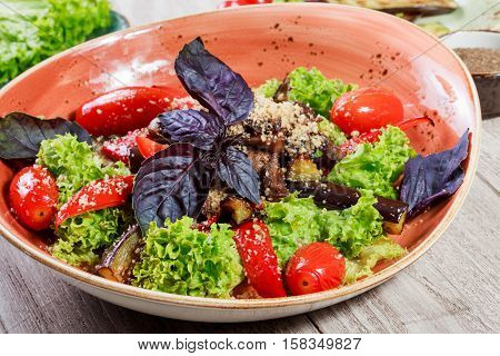 Hot salad with grilled tomatoes eggplant zucchini red pepper salad leaves garnished with grated walnuts and basil and glass of wine on wooden background. Healthy salad