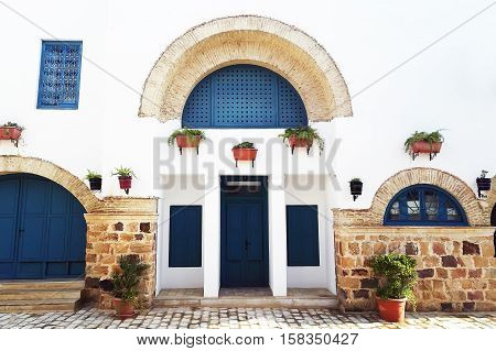 Tunisian eastern courtyard houses with white walls and blue windows doors decorated with plants