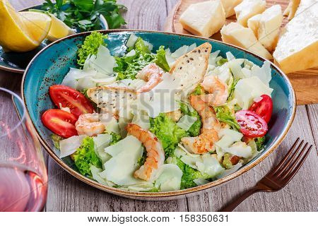 Shrimp salad with parmesan cheese croutons tomatoes mixed greens lettuce and glass of wine on wooden background. Healthy food