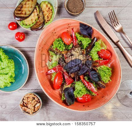 Hot salad with grilled tomatoes eggplant zucchini red pepper salad leaves garnished with grated walnuts and basil and glass of wine on wooden background. Italian food. Top view