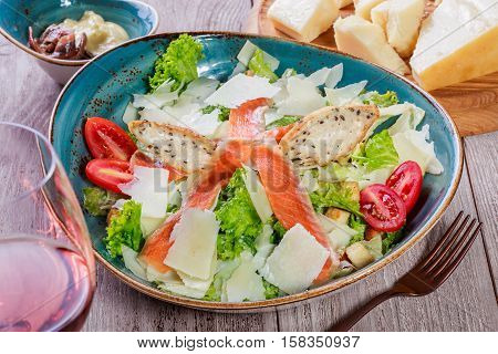 Salmon salad with tuna sauce parmesan cheese croutons tomatoes mixed greens lettuce and glass of wine on wooden background. Mediterranean food