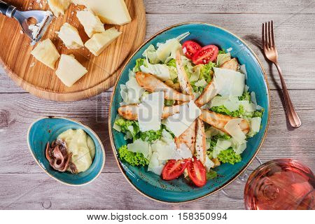 Salad with chicken breast parmesan cheese croutons tomatoes mixed greens lettuce and glass of wine on light wooden background. Ingredients on table. Top view