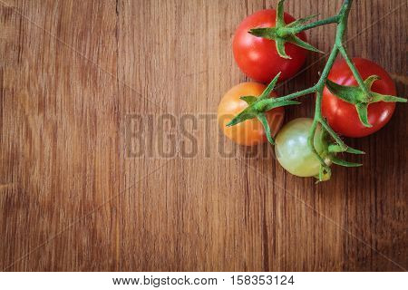 Bunch of ripening red tomatoes on wooden table background