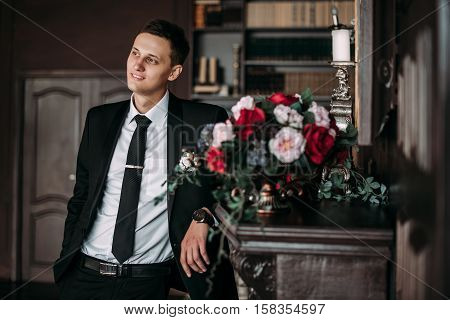 Groom in a suit holding buttonhole in the library