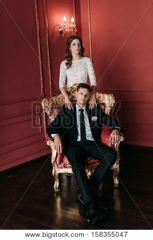Cute Wedding Couple In The Interior Of A Classic Studio With Red Background . Hey Kiss And Hug Each
