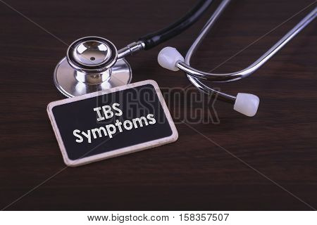Medical Concept- IBS Symptoms words written on label tag with Stethoscope on wood background