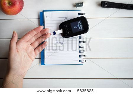 Woman checking sugar level with glucometer. Diabetes test. Healthcare, diabetes, medical concept.