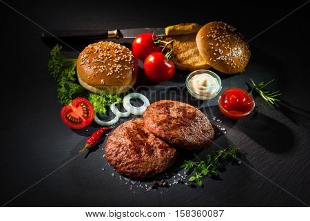 Homemade hamburger. Grilled beef patties, sesame buns with other ingredients for hamburgers on dark slate plate