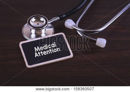 Medical Concept- Medical Attention words written on label tag with Stethoscope on wood background