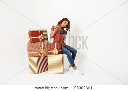 Young beautiful girl sitting on big gift box opening smaller one Isolated Copy space