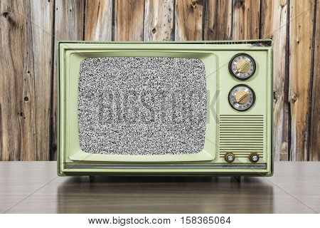 Grungy green vintage television set with wood wall and static screen.