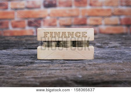 Business Concept - FINANCE word Golden coin stacked with wooden bar on shallow brick background