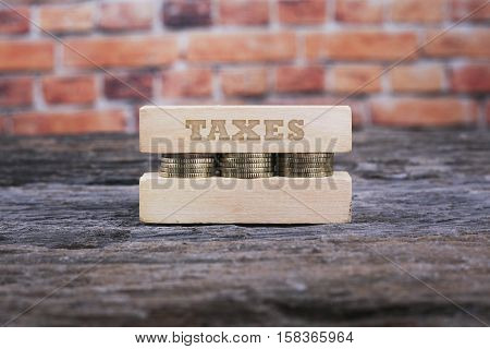 Business Concept - Taxes Word Golden Coin Stacked With Wooden Bar On Shallow Brick Background.