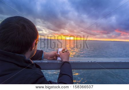 Man writing in a notebook at sunset - Colorful sunset over the Bodensee lake and a man writing in a spiral notebook while admiring the horizon.