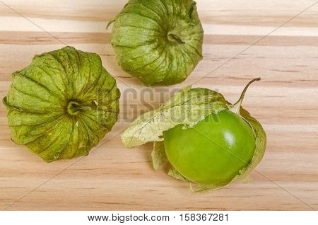 Three Whole Green Husk Tomatoes, one with loose husk on table