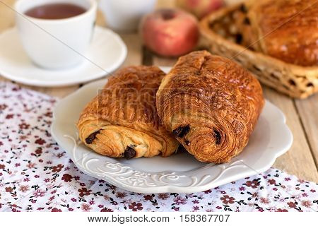Chocolate croissants (pain au chocolat) on a plate with tea for breakfast