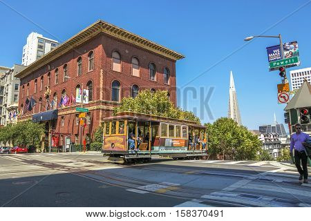 San Francisco, California, United States - August 17, 2016: a Cable Car cross to California and Powell streets near University Club of San Francisco. On background, the Transamerica Pyramid.