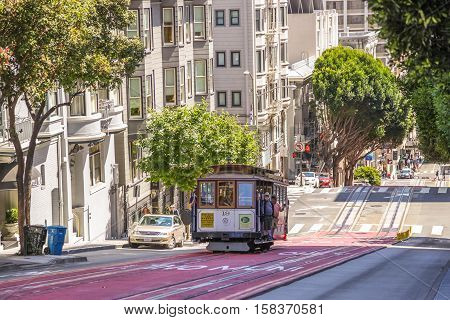 San Francisco, California, United States - August 17, 2016: passengers enjoy a ride in Cable Car on Powell Street, the most famous and tourist tram line of San Francisco in a sunny day.