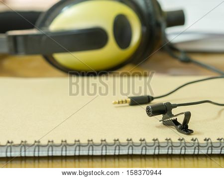 Clip Microphone On The Book And Headphones On The Table . Sounds Concept.