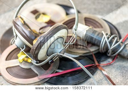 Vintage broken headphones with microphone and tapes