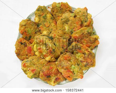Healthy baked vegan vegetable pakoras on plate, top view.